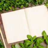 Kochbuch und grüne Kräuter